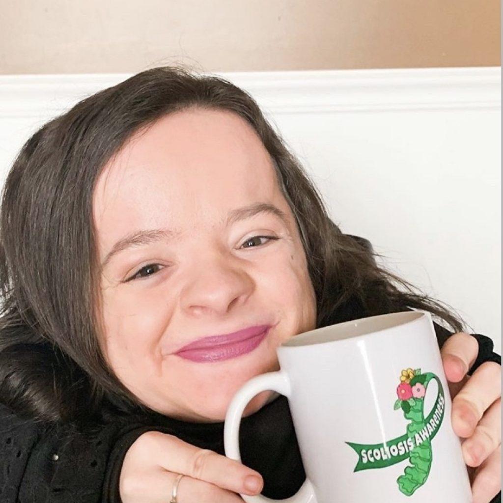 Michaela Davert smiling with scoliosis awareness mug