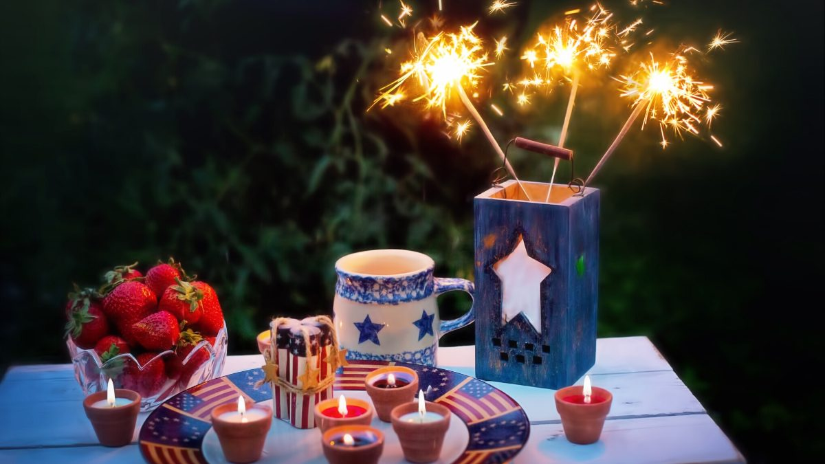 4th of July table setting with strawberries, festive candles, and sparklers in a blue vase.